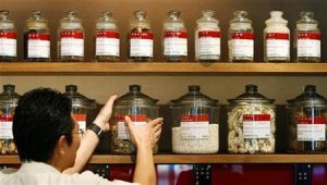 Shop assistant arranges jars containing roots and herbs at Chinese medicine shop in Singapore